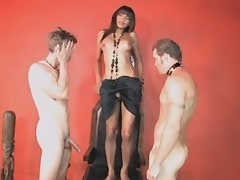 Hot shemale does perfect blowjob to two slave guys