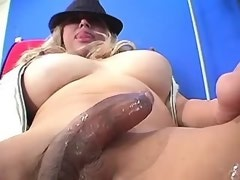 Breasty tranny in leather trousers plays with cock