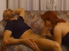 Redhead shemale slut in leather sucks dude on sofa